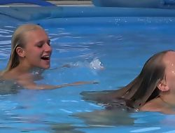 Two beautiful girls swimming and licking wits the pool